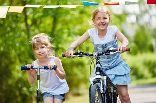 Mädchen fahren mit Roller und Fahrrad