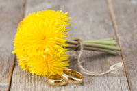 Wedding rings and bunch of yellow dandelion flowers