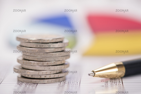 stacked euro coins with data and chart of exchange market