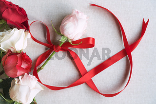 Roses and red ribbon in shape of infinity