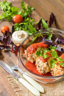 Yummy looking cooked stuffed pepper served in a transparent glass pot on a wooden table