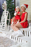 happy mom and daughter in Santa's suits are sitting under snow