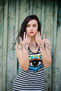 Brunette model girl at dress with stripes background cian wooden background.
