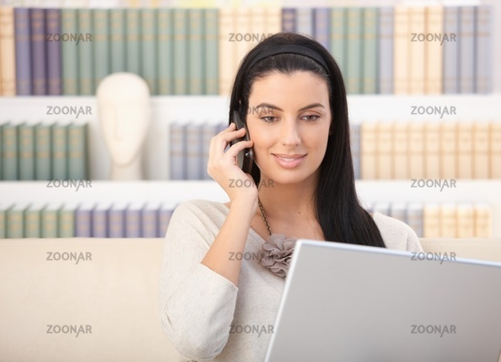 Smiling woman with laptop and mobile phone