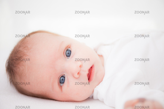 Cute adorable newborn baby girl in white bed and looking at the camera
