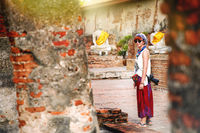 Travel lifestyle. Women with camera walk along ancient temples in the day time temple in Ayutthaya.