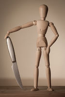 A wooden jointed doll with a shiny sharp knife.