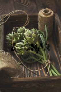 Supplies and materials for artichoke bouquet on wooden background. Top view.