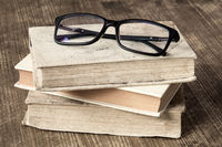 Stack of books with reading glasses
