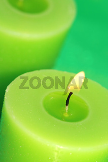 green burning candles on background
