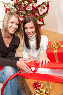 Two women packing Christmas present
