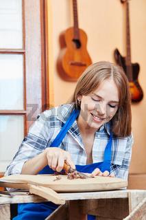 Junge Frau in der Gitarrenbauer Lehre