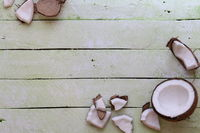 halved coconuts on green wood table background