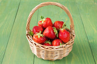 Basket of strawberries on green wooden background