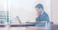 Elegant businessman analyzing data in modern office.