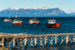 Colourful wooden fishing boats in the harbour at Puerto Natales port