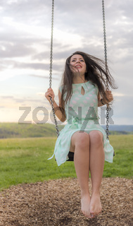 Happy young woman on a swing at sunset