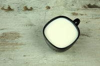 A cup of milk on old wooden yable