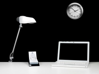 A contempory workplace office desk with a black background