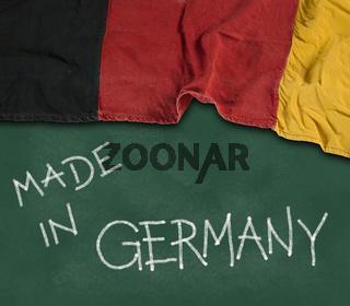 fahne von deutschland und text made in germany auf kreidetafel