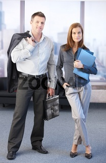 Young colleagues standing in office lobby smiling