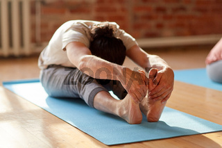 man doing yoga forward bend at studio or gym