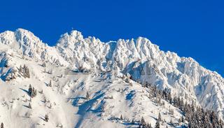 High mountain with summit cross under deep snow in winter. Rauhhorn, Allgau, Bavaria in Germany.