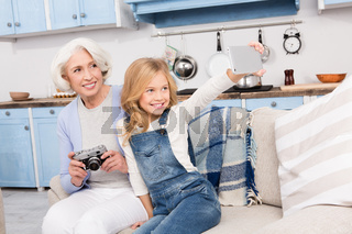 Grandmother and granddaughter making photos