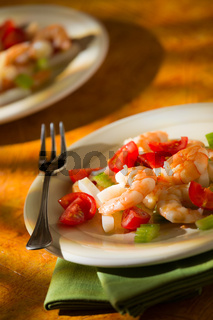 Shrimp salad with squid tomatoes and celery over a green napkin