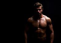 Young muscular fit sportsman posing shirtless on black backgroun