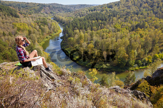 Young blonde woman tourist  sitting on a cliff with map in hands on background of siberian autumn landscape with the river Berd