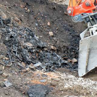 Former rubbish dump in the excavation pit, black discoloured and contaminated soil, old landfill with waste in a construction site
