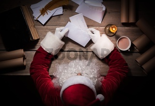 Santa Claus sitting at the table in his room and opening Christmas letter from child