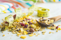 Tasty homemade muesli with nuts in bowl with measuring tape.