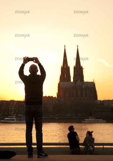 man taking smartphone picture of cathedral at sunset, Cologne, North Rhine-Westphalia, Germany