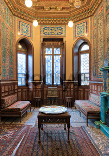 Manial Palace of Prince Mohammed Ali. Winter room at the Residence Hall, with ornate wall and ceiling, windows, decorated couches, tea tables and ornate carpet, Cairo, Egypt