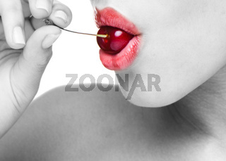 beauty female face with cherry in her mouth