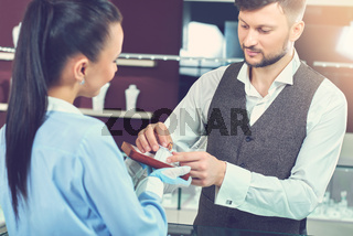 Man holding ring and choosing present at jewelry store.