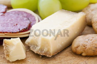 Mountain cheese with grapes and salami as closeup on a chopping bread