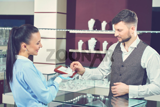 Female seller in jewelry store showing golden ring for buyer.