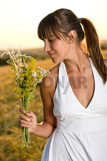 Romantic brunette woman in sunset corn field