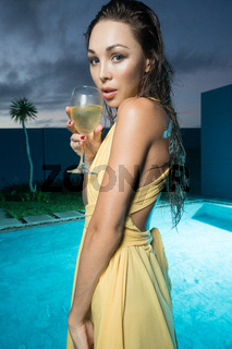 Beautiful brunette woman in yellow dress by the pool
