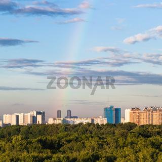 rainbow in blue sky over modern houses