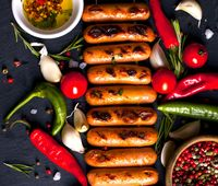 Fried sausages with herbs, spices and vegetables on black background