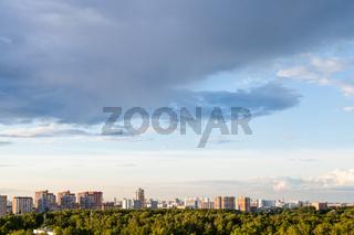 rainy gray cloud in blue evening sky over city