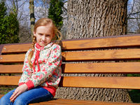 Small girl sits on the bench