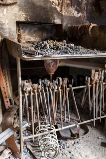 Forge with a hearth and old pliers and tools in a workshop
