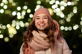 happy young woman over christmas tree lights