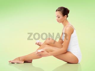 woman applying moisturizing cream to her leg