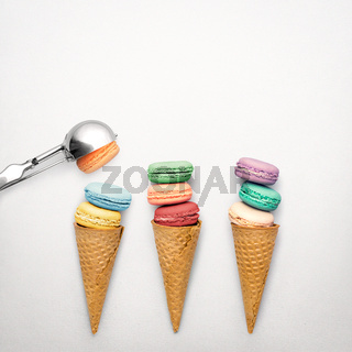 Creative still life photo of three waffle cones with macaroons and spoon on grey background.